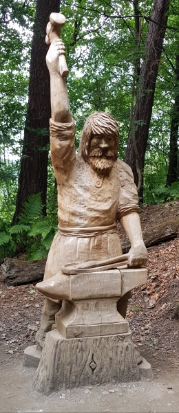 Wood carving commemorating Scotland's first metal workers by Iain Chalmers on the Wallace Way, Abbey Craig
